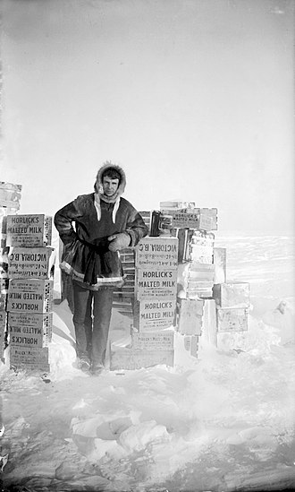 Horlicks - Explorer Ernest de Koven Leffingwell poses with cases of Horlick's Malted Milk on Flaxman Island, Alaska, circa 1910
