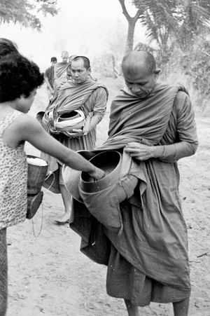 Ajahn Maha Bua - Ajahn Maha Bua led the monks (in this photo, he was follow by Phra Maha Amborn Ambaro, later the 20th Supreme Patriarch of Thailand) for morning alms around Baan Taad, Udon Thani, in 1965.