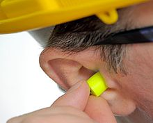 A picture of a man's head, focused on the ear, with yellow ear plugs being inserted into that ear.
