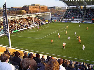 Milton Keynes Dons F.C. - Milton Keynes Dons (white) take on Blackpool (tangerine) at the former England National Hockey Stadium during the 2004–05 season
