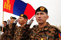 Mongolian Army soldiers salute while their nation's flag waves in the breeze at the Transit Center at Manas.jpg