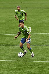 Two men in blue and green soccer uniforms. One has the ball at his feet and is looking upfield.