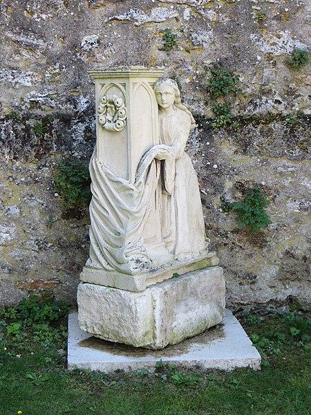 Statue posée au pied du mur nord