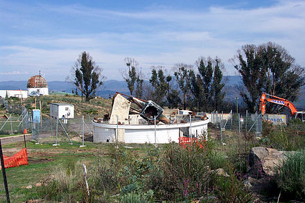 White circular building missing roof, with large metal debris in center, surrounded by chain-link fence