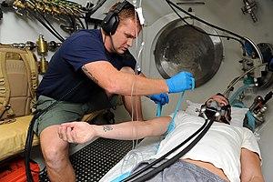 Fotografía del interior estrecho de una cámara de descompresión con un ayudante médico del hospital preparando a un paciente para una vía intravenosa durante una demostración de atención al paciente por enfermedad por descompresión.