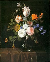 Flowers in a glass vase on a partly draped stone ledge