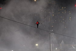 A man on a tightrope with mist and lights in the background