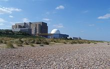 Nuclear power station next to shingle beach. A large factory-like concrete building with a prominent white dome in front.