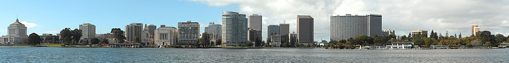 Daytime skyline of a city behind a lake, showing several tall skyscrapers in the middle of the image, with several low-rises on the left and trees on the right.