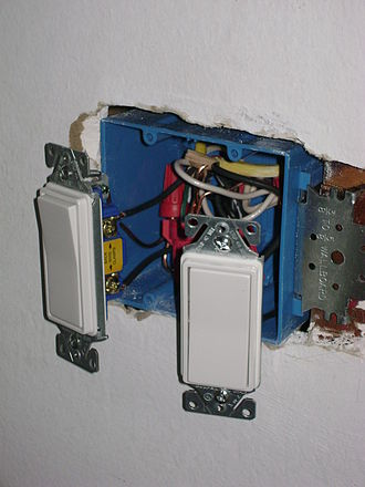 "Light switch - Two Lutron decorator-style rocker switches and wiring (often called ""Decora switches"", after the trademarked Leviton switches), as installed in the United States. Shown here will be fastened to this recessed, non-metallic box, then a cover plate is installed. This ""double gang"" (two unit) installation uses non-metallic-sheathed cable and twist-on wire connectors."