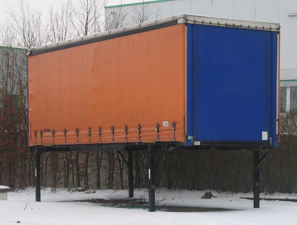 Mobile Wechselbrücke auf vier Füßen in den Farben orange und blau