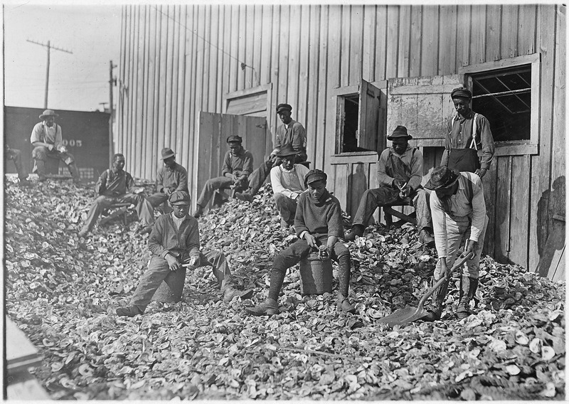 Oyster shuckers at Apalachicola, Fla. This work is carried on by many young boys during the busy seasons. This is a... - NARA - 523162