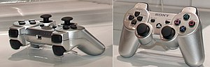 "Sixaxis - Prototype silver Sixaxis controller as shown at the CES 2006, which did not feature ""Sixaxis"" branding on the top."