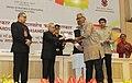 "Pranab Mukherjee presenting the Rajat Kamal Award for Best Biographical Film ""Aamaar Katha Story of Binodini"" in Non Feature Films Section to the Director, Shri Tuhinabha Majumdar, at the 62nd National Film Awards Function.jpg"