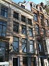 foto van Huis met zandstenen gevel met hardstenen onderpui en rechte lijst waarop attiek