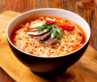 Shin Ramyun - A bowl of red Shin Ramyun with toppings including beef, shitake mushrooms, red peppers, and scallions