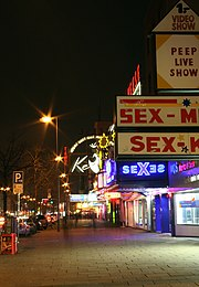 "The Reeperbahn nightclub as seen from the sidewalk with its entrance lighted. Theatre marques say ""Sex"" and ""Peep live shows""."