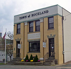 "A square-fronted building in gold brick with two central pilasters. ""Town of Rockland"" is in large letters across the top, with ""Livingston Manor National Bank"" in small letters close to the ground floor"