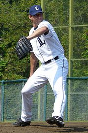 "A man wearing a white baseball uniform with a navy blue ""L"" on the chest, a navy blue cap with a white ""L"" on the center, and a black glove on his left hand in the midst of pitching a ball"