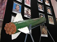 Sderot - A Qassam rocket is displayed in Sderot town hall against a background of pictures of residents killed in rocket attacks