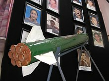 Sderot - A Qassam rocket is displayed in Sderot town hall against a background of pictures of residents killed in rocket attacks.jpg