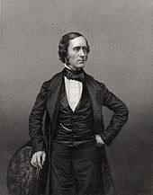 photograph of standing figure facing right, left hand on hip, right hand resting on chair