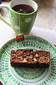 Slice of banana date bread on green plate with tea.jpg