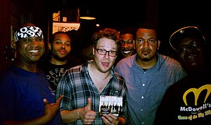 "The Soul Rebels - Actor Seth Rogen holding up a copy of the ""Unlock Your Mind"" CD and hanging out with The Soul Rebels at Le Bon Temps Roule in 2012"