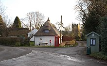 Village centre with two thatched single story cottages with white walls, a red phone box, a red post box and a greenish wooden bus stop shelter with a pitched roof