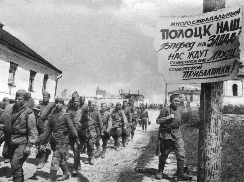 Soviet soldiers in Polozk (Belarus), passing by propaganda poster celebrating the reconquest of the city and urging the liberation of the Baltic from Nazi German occupation. July 4, 1944