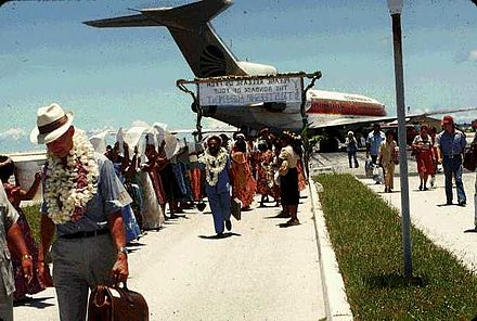"Arrival of UN Visiting Mission, Majuro, 1978. The sign reads ""Please release us from the bondage of your trusteeship agreement."" TTPI UN Mission 1978.jpg"