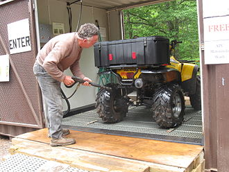 Rider cleaning an ATV at a U.S. Forest Service pressure washer station to prevent the spread of invasive plants. TV rider using power wash station.jpg