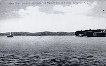 "A black-and-white illustration showing the lighthouse at left surrounded by water and the shore at right. Faint writing across the top reads ""Hudson River, showing Lighthouse and Maxwell–Briscoe factory, Tarrytown, N.Y."""