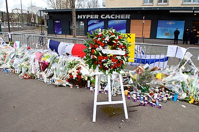 a wreath of flowers that highlight many other gifts of flowers and candles outside a short metal fence around the area of investigation