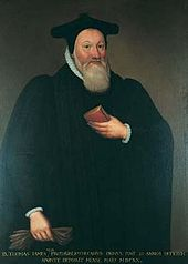 A man with full beard, wearing a black pointed cap and robes. He is holding a book in his left hand against his body, and a pair of gloves in his right hand by his side