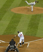 The moment of contact between Thome's bat and a pitch from Roberto Hernandez; the image is distorted through the black screen protecting those sitting behind home plate.