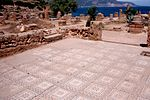 A mosaic made of tiles covers the ground of a small square near a grave site.