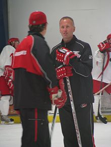 A man wearing a black shirt & black pants is standing on a hockey rink. He has red gloves and is holding a stick. He is talking to a man whose back is to camera.