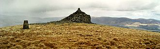 Carsphairn and Scaur Hills - Trig point and spiral cairn on top of Cairnkinna with a squall coming in from the Lowthers.