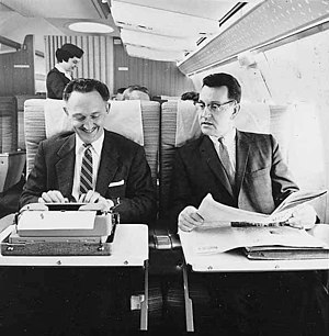 Two men on Northwest Airlines aircraft, one using typewriter, with female flight attendant in background (4670206226).jpg