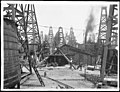 Two men standing near a wooden shed in the midst of dozens of oil derricks in a Los Angeles oil field (CHS-1276).jpg