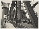 Two women and a child on the walkway of the Sydney Harbour Bridge, 1932 (8283753516).jpg