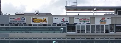 Five banners in a row at the top of the stadium press box with dates and logos for each bowl game, presented in chronological order from left to right