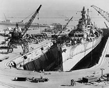 A shipyard with a large dry dock occupied by a massive gunship. Crewmen can be seen on the battleship's deck, while dock equipment such as cranes and trucks can be seen lining the sides of the drydock; in the distance a pier can be seen, while two smaller ships are visible in the background of the image.
