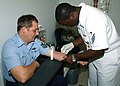 US Navy 030623-N-1126D-003 Hospital Corpsman Seaman Terrence Williams from Camilla, Ga. draws blood from Ship Serviceman 1st Class Ronald Spears from Dickinson, Texas at medical aboard Naval Air Station, Jacksonville, Fla.jpg
