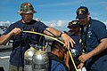 US Navy 030626-N-0493B-007 Operations Specialist 2nd Class Matthew Medeiros, left, and Boatswain's Mate 1st Class Hans Jacobs assist Royal Brunei Navy (RBN) diver Cpl. Heidi with preparations for a training dive.jpg