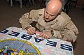US Navy 050312-N-6027E-001 Lt. Cmdr. David Oravec, the Navy Chaplain assigned to Naval Mobile Construction Battalion Two Three (NMCB-23), signs a Seabee flag.jpg