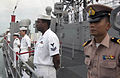 US Navy 060618-N-9851B-004 Royal Thai Navy Liaison Officer, Lt. Ittikorn Buanuam, right, stands with USS Tortuga (LSD 46) Sailors manning the rails as the amphibious dock landing ship enters port.jpg