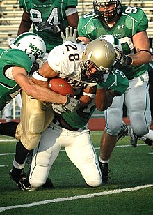 An American Football player in a gold and white uniform attempts to run past three defenders in green and white uniforms.
