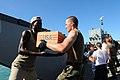 US Navy 080922-N-7955L-073 Hospital Corpsman 3rd Class Mikel Frazier, an individual augmentee assigned to the amphibious assault ship USS Kearsarge (LHD 3), moves boxes of cooking oil.jpg